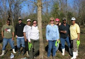 After a morning of clearing the scout camping area along Woodlands Trail,  Rosina Philippe (far right) America's Wetland Conservation Corps and volunteers prepare to tag the trees they planted that were donated by the Chevron Tree Farm.